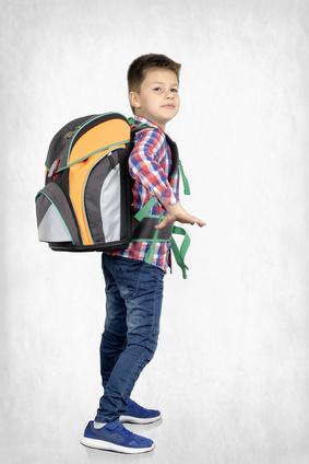 Schulkind mit schwere Schulranzen